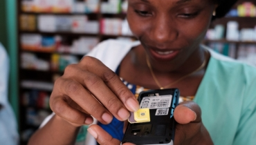 A woman inserting a new SIM card into a mobile phone in Abidjan, Côte d'Ivoire. Photo © Nyani Quarmyne/International Finance Corporation